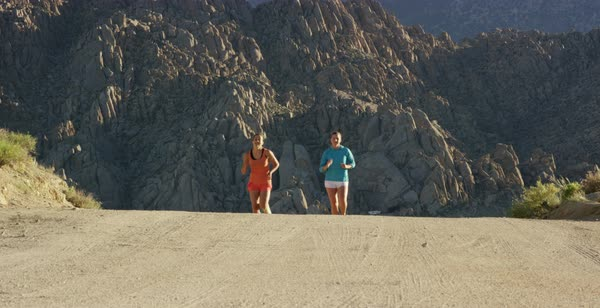 Static shot of two women running toward camera on a dirt road in Alabama Hills Royalty-free stock video