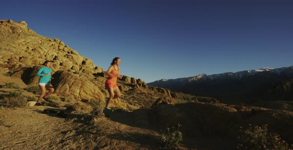 Panning shot of two women running on rocky terrain in Alabama Hills Royalty-free stock video