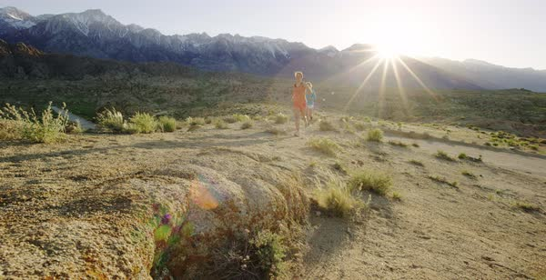 Panning shot of two women running in Alabama Hills Royalty-free stock video