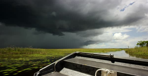 Hand-held shot of storm clouds gathering over a marsh seen from a moving boat Royalty-free stock video