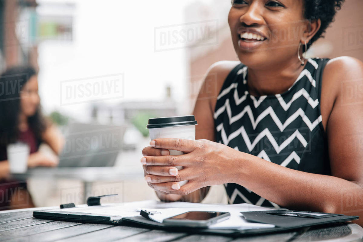 Smiling businesswoman drinking coffee at sidewalk cafe Royalty-free stock photo