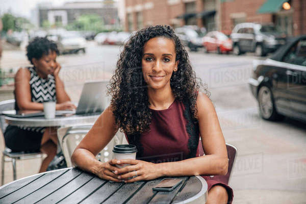 Portrait of smiling businesswoman drinking coffee at sidewalk cafe Royalty-free stock photo