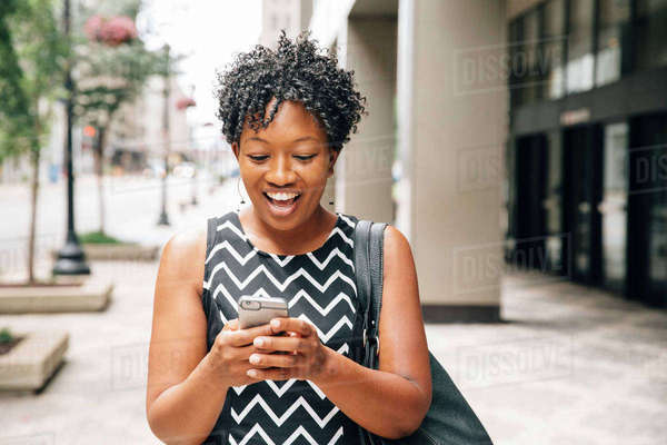 Surprised businesswoman standing on city sidewalk texting on cell phone Royalty-free stock photo