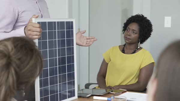 Hand-held shot view of a team of office workers holding a meeting on solar energy project Royalty-free stock video