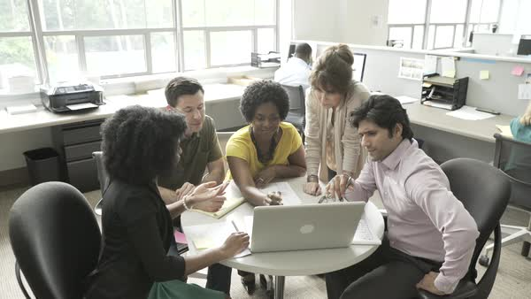 Hand-held shot view of a team of office workers looking at a laptop together and changing ideas on a project Royalty-free stock video