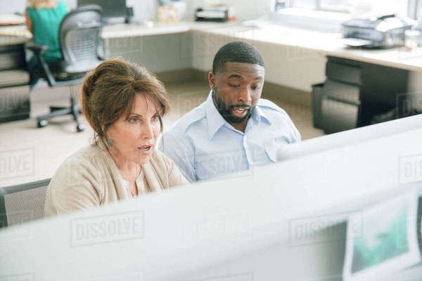 A man and a woman sitting at a computer in an office Royalty-free stock photo