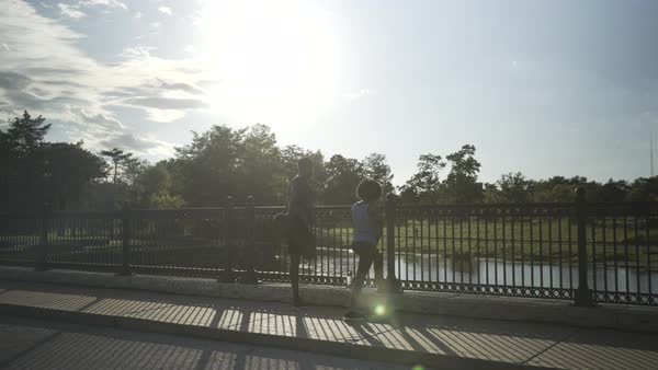 Gimbal shot of a man and a woman stretching on a bridge Royalty-free stock video