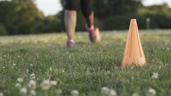 Hand held shot of a woman running between orange cones in a park Royalty-free stock video