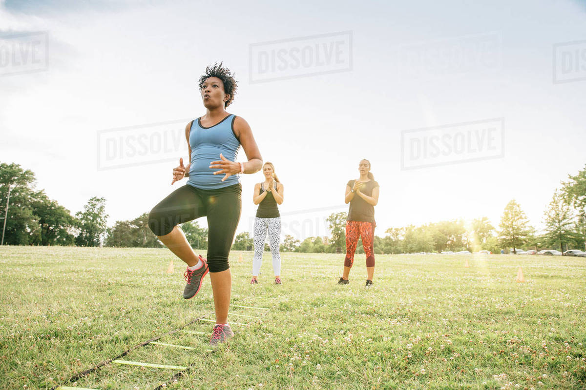 Friends encouraging woman running ladder in field Royalty-free stock photo