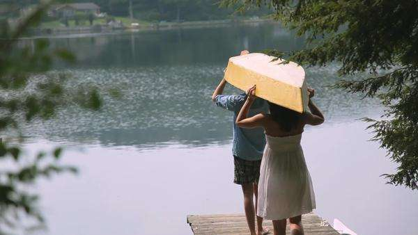 Couple carrying canoe on wooden dock over lake Royalty-free stock video