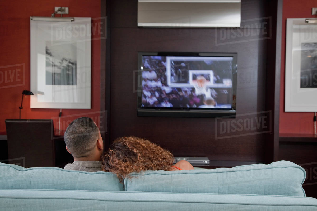 Couple Watching Basketball Game On Television In Living Room Stock Photo Dissolve