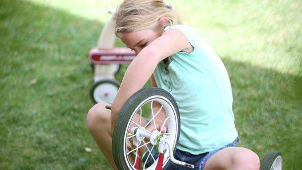 Girl tying streamers to tricycle wheel Royalty-free stock video