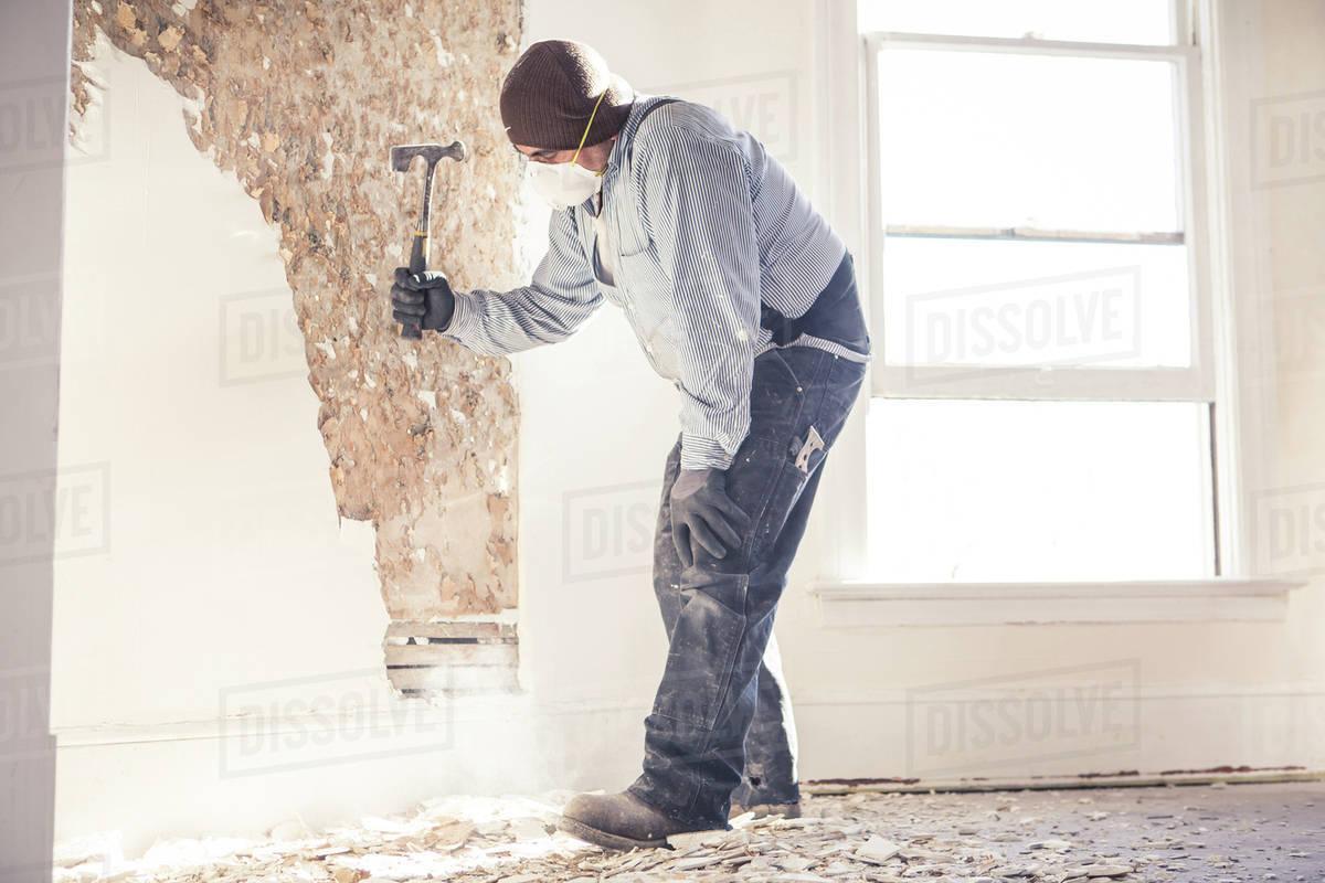 Hispanic construction worker hammering wall Royalty-free stock photo