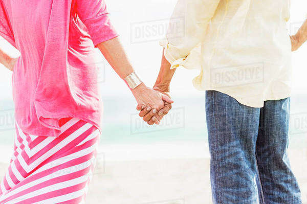 Older couple holding hands on beach Royalty-free stock photo