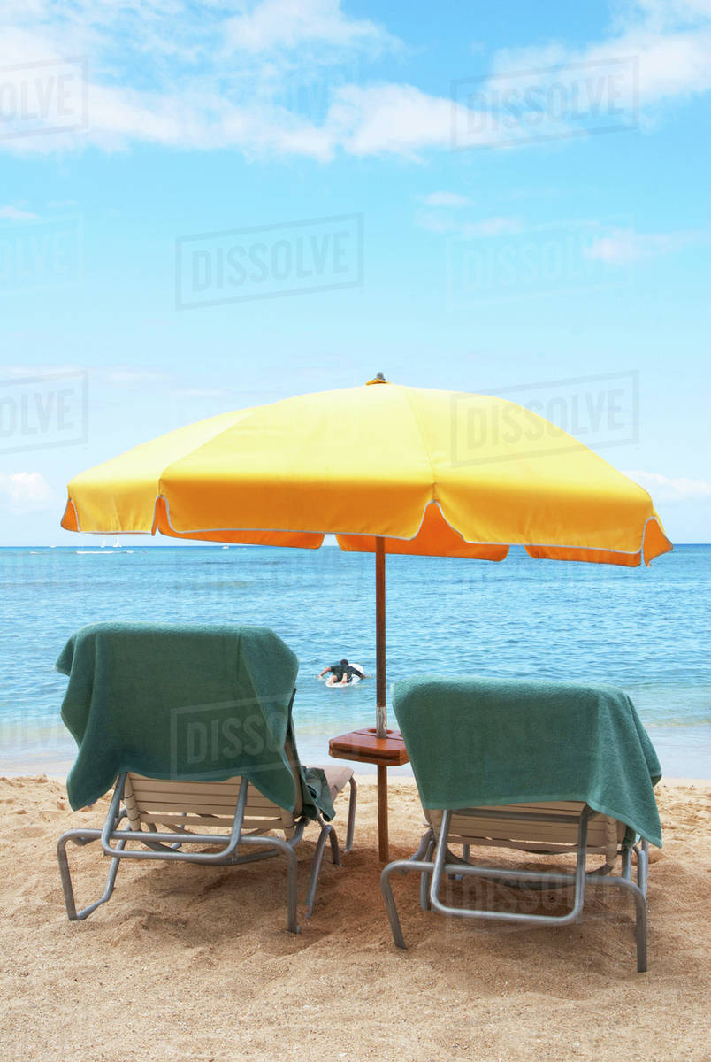 Lawn Chairs And Umbrella On Beach