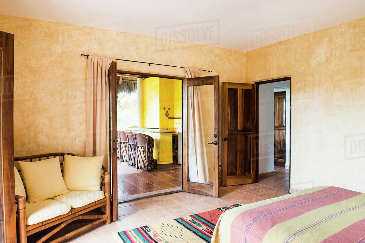 Open Doors, Bed And Loveseat In Bedroom