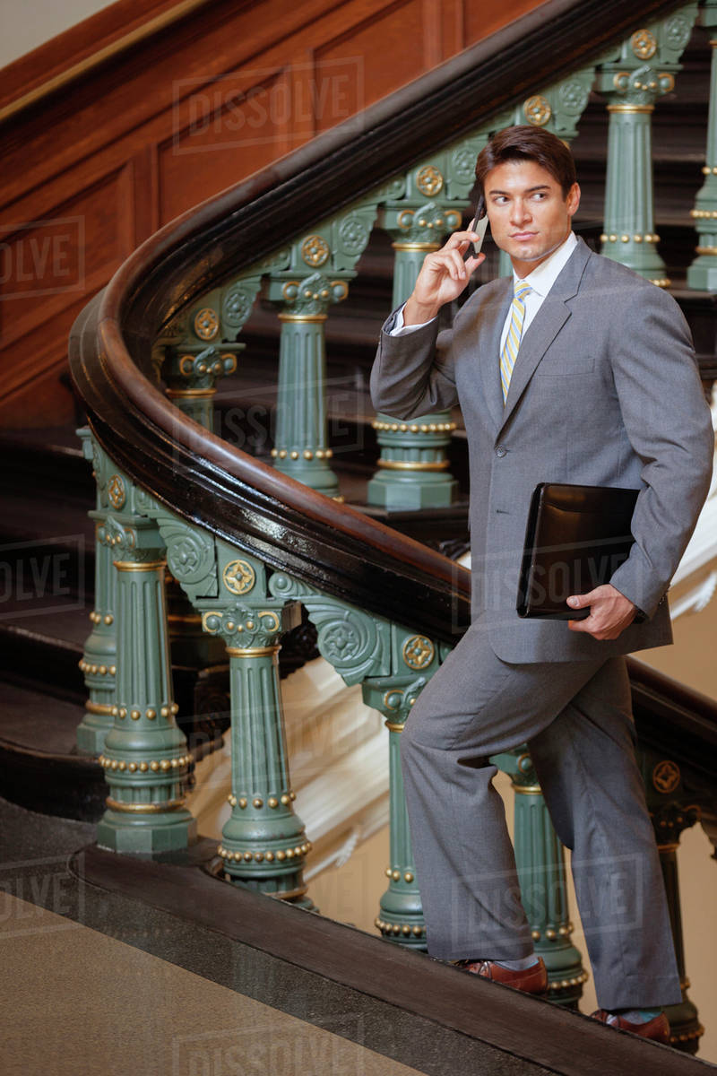 Hispanic Businessman Talking On Cell Phone On Ornate Staircase