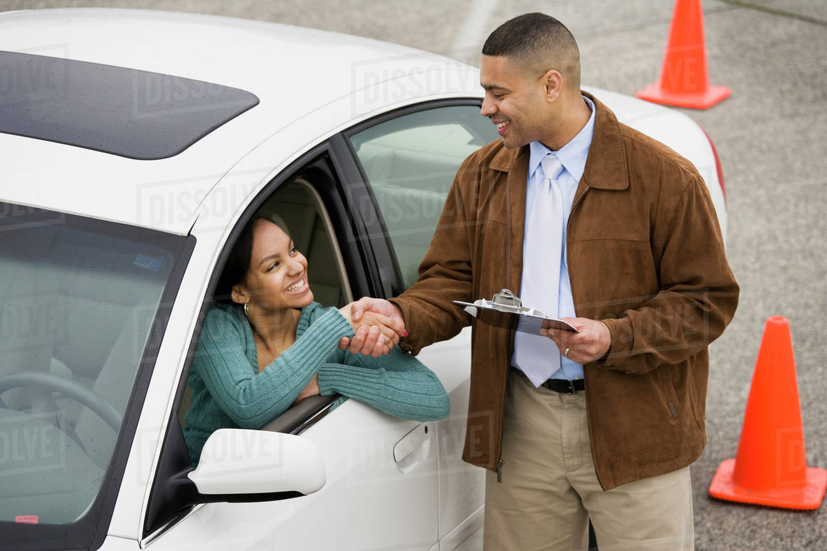 African teenager shaking hands with driving instructor stock photo