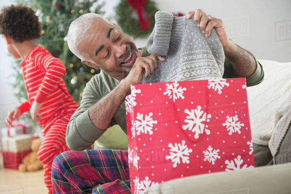 Mixed race grandfather and grandson opening Christmas gifts Royalty-free stock photo