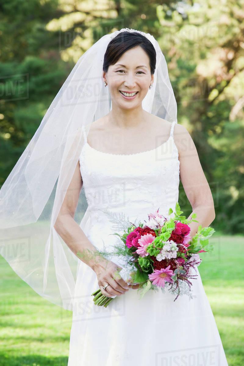 Asian bride holding bouquet - Stock Photo - Dissolve