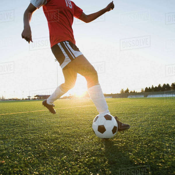 Mixed race woman kicking soccer ball Royalty-free stock photo