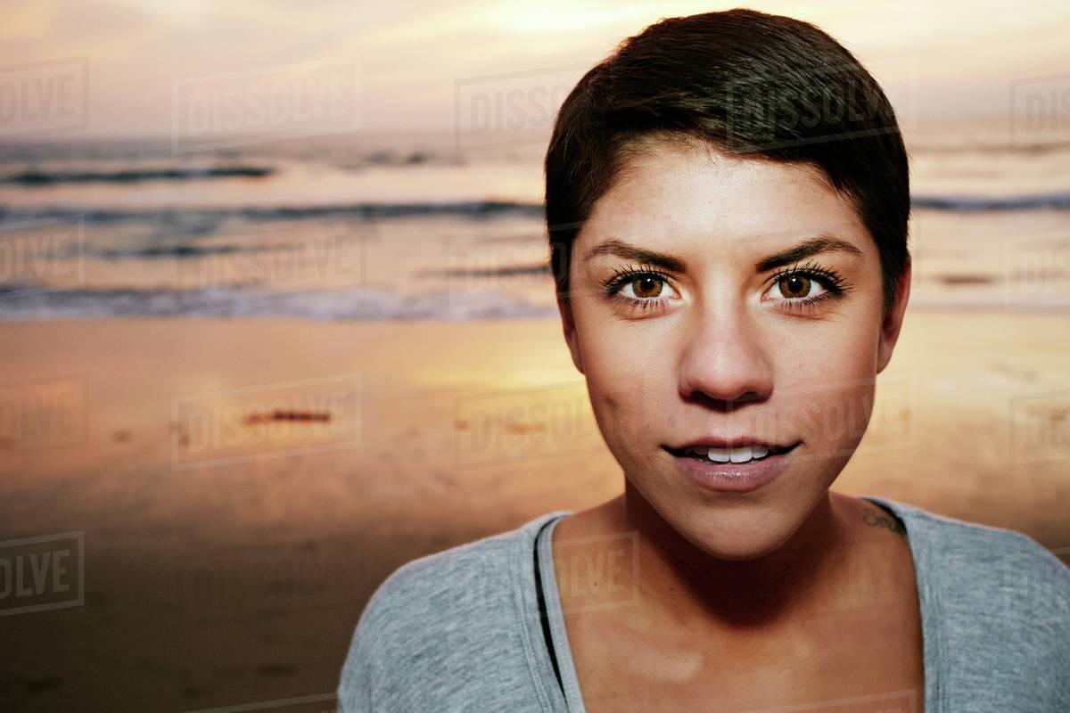 Serious Hispanic woman standing on beach Royalty-free stock photo