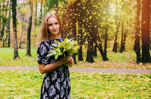 Caucasian woman carrying bouquet in park Royalty-free stock photo