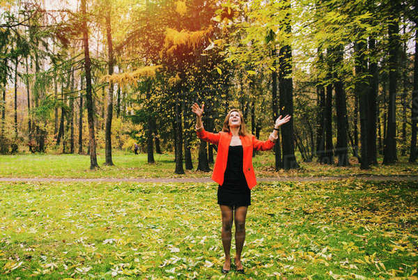 Caucasian woman tossing autumn leaves in park Royalty-free stock photo
