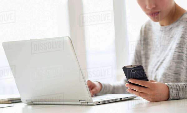 Hispanic woman using cell phone and laptop Royalty-free stock photo