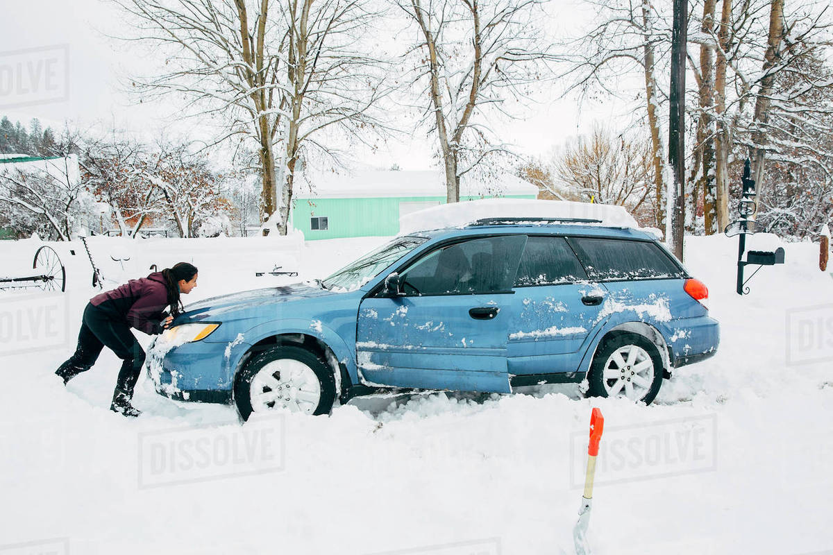 caucasian woman pushing car stuck in snow stock photo dissolve