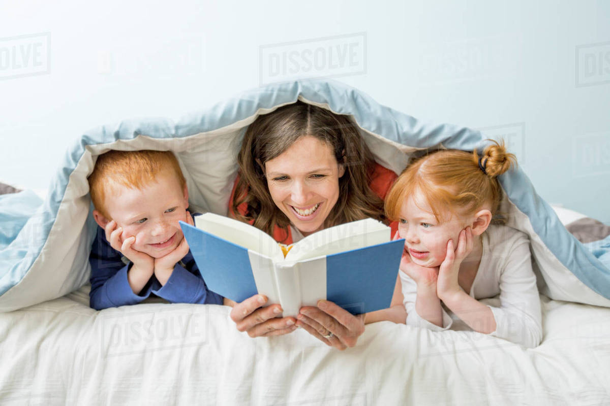 Caucasian Mother And Children Reading Book In Bed D145 194 073
