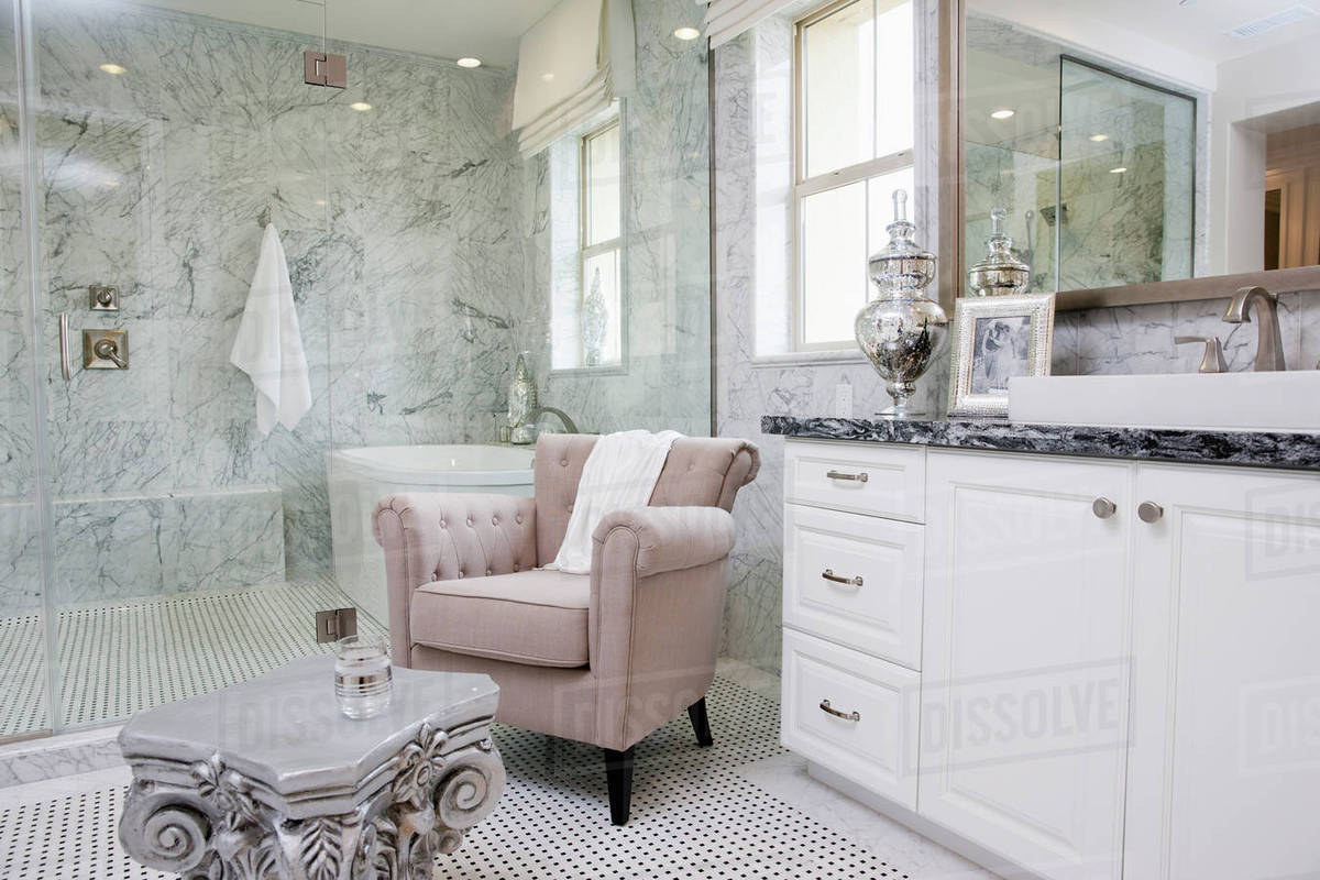 Sitting Area With Bathtub Across The Glass Wall In The Bathroom