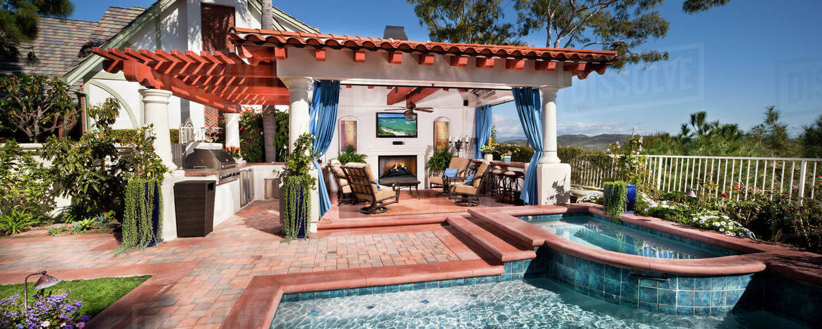 Sitting area at covered patio with swimming pool in foreground stock photo