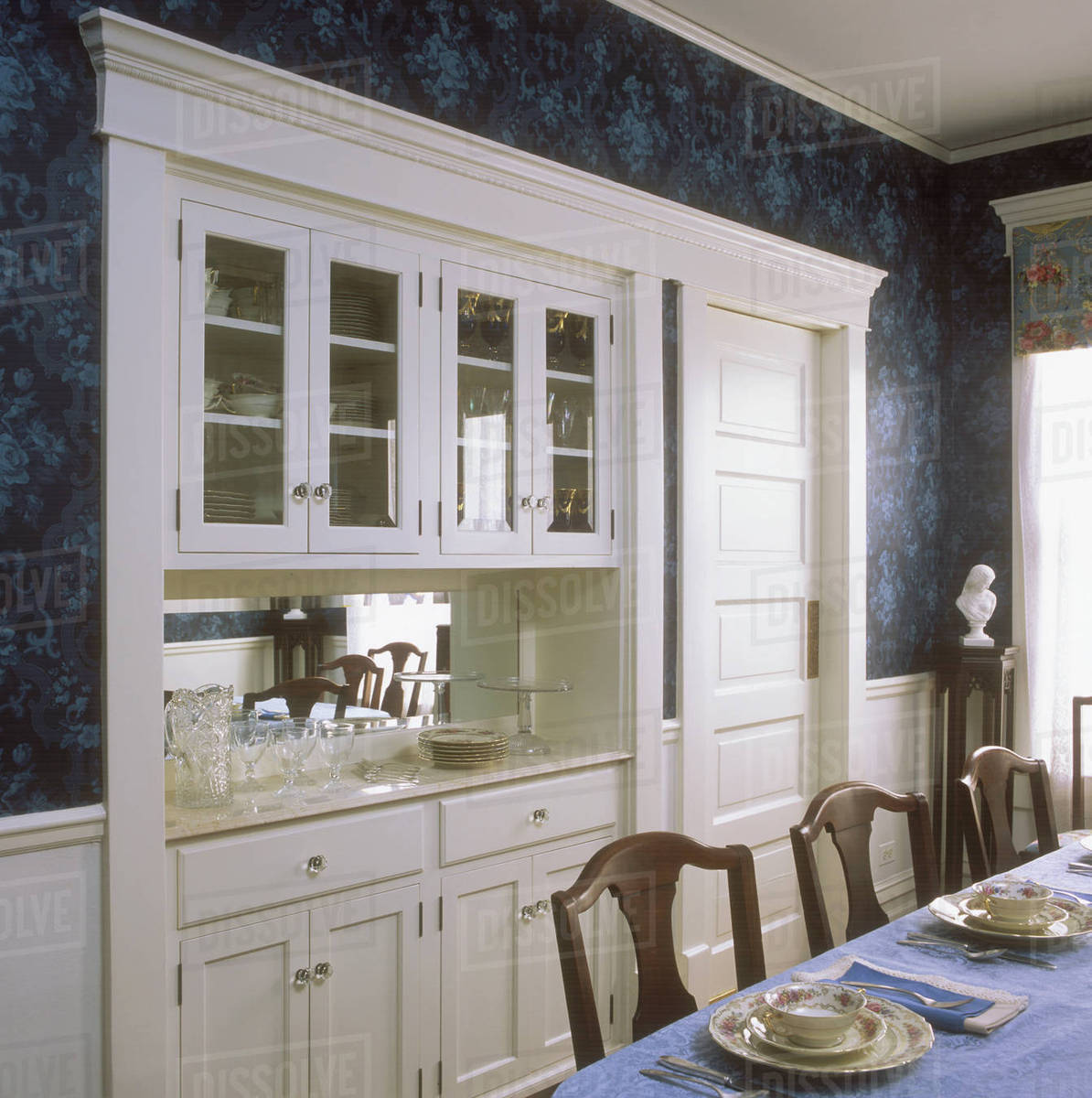 A Built In China Cabinet And Buffet In A Restored Victorian Dining Room All Wood Is Painted White Dark Blue Patterned Wallpaper Swing Door Divides Dining Room From Kitchen Stock Photo