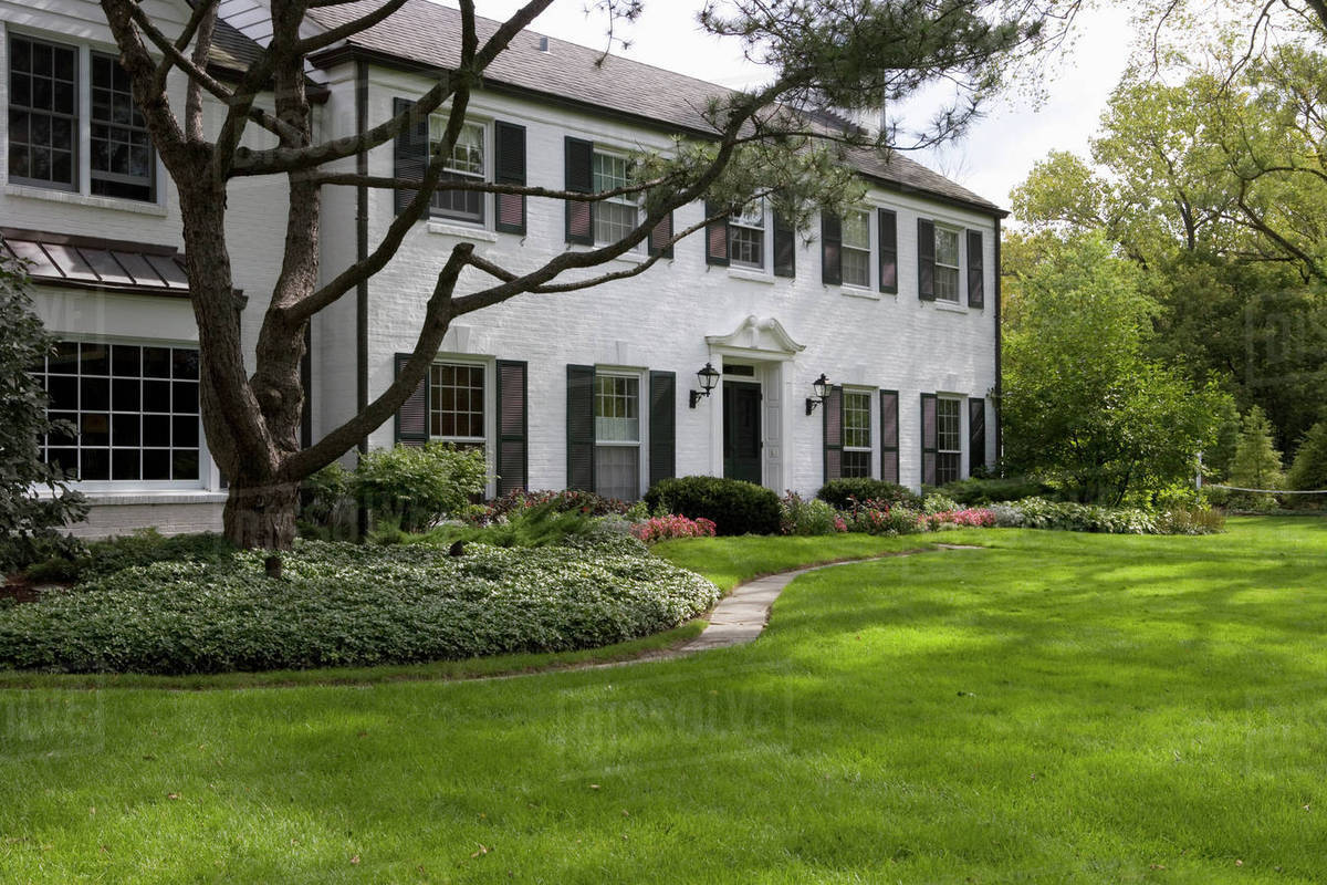White Brick Traditional Colonial Home With Black Shutters Pediment Above The Door