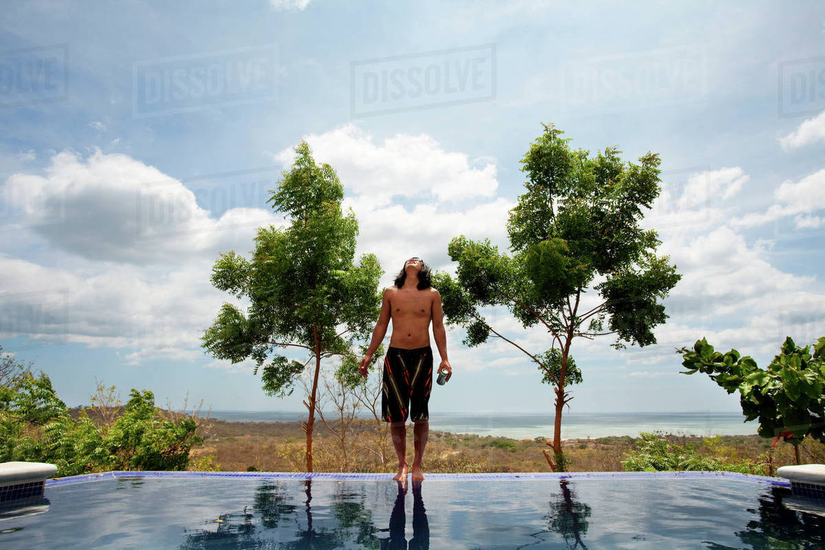 Asian man standing on edge of infinity swimming pool stock photo