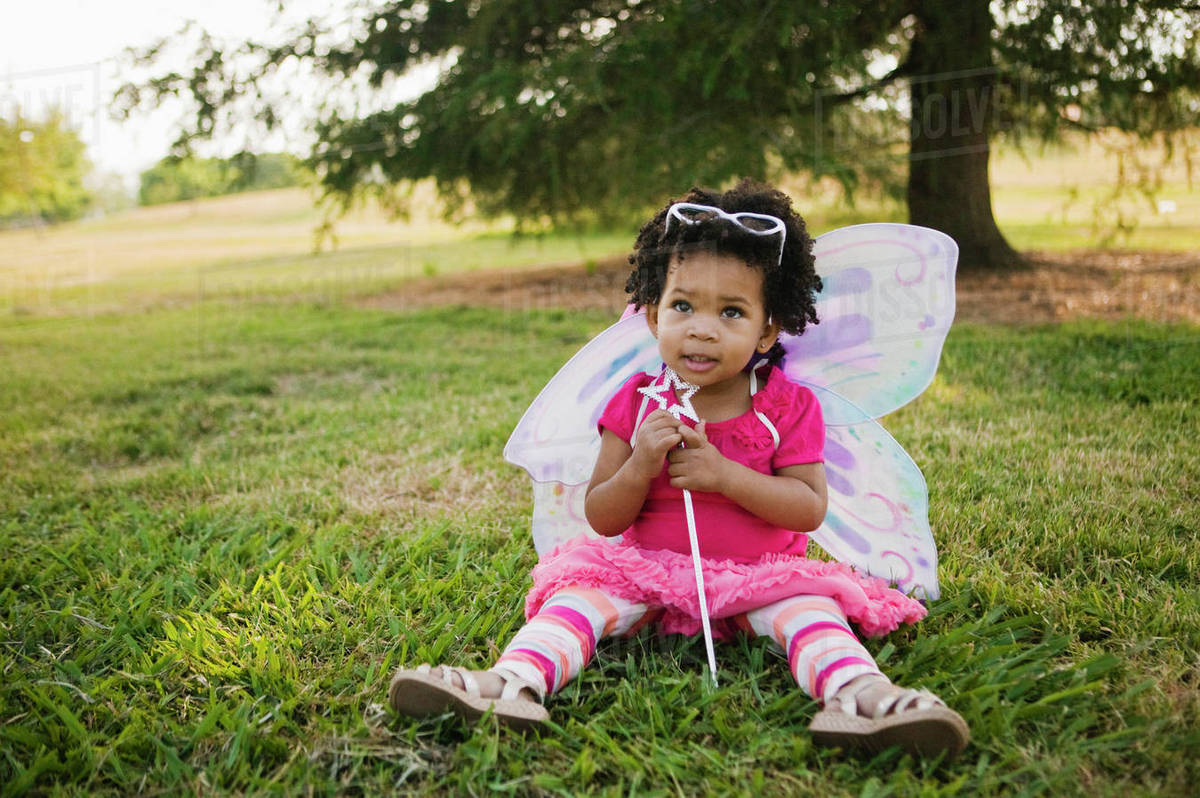 Black baby girl in fairy costume in park Royalty-free stock photo