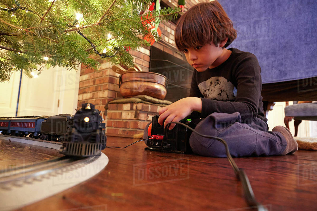 mixed race boy playing with train under christmas tree - Train Under Christmas Tree