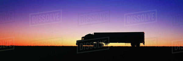 Silhouette of semi-truck against dramatic sky Royalty-free stock photo