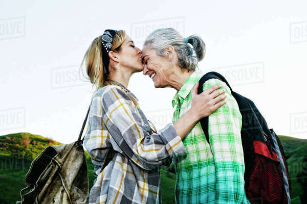 Caucasian daughter kissing mother on rural hilltop Royalty-free stock photo