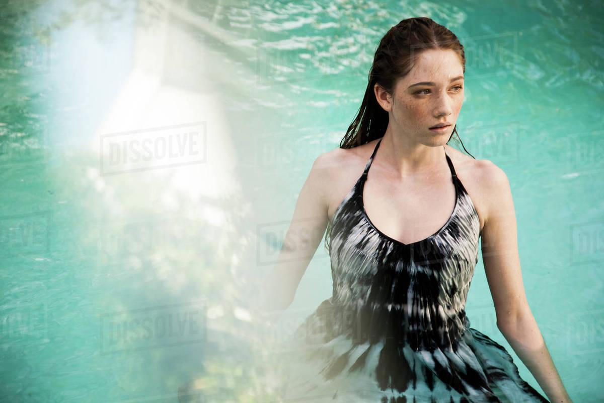 feab11fc02 Caucasian woman wearing dress in swimming pool - Stock Photo - Dissolve