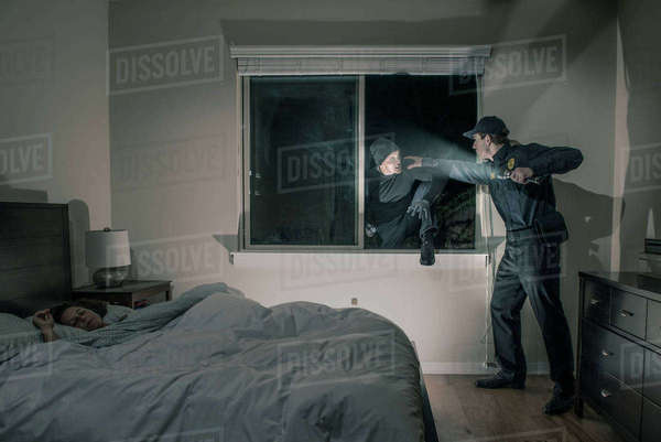 Caucasian police officer shining flashlight on house burglar Royalty-free stock photo