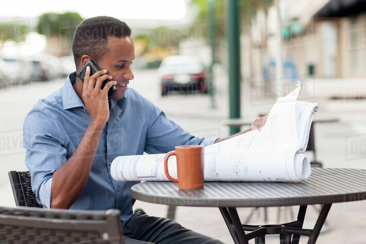Black architect talking on cell phone and reading blueprints Royalty-free stock photo