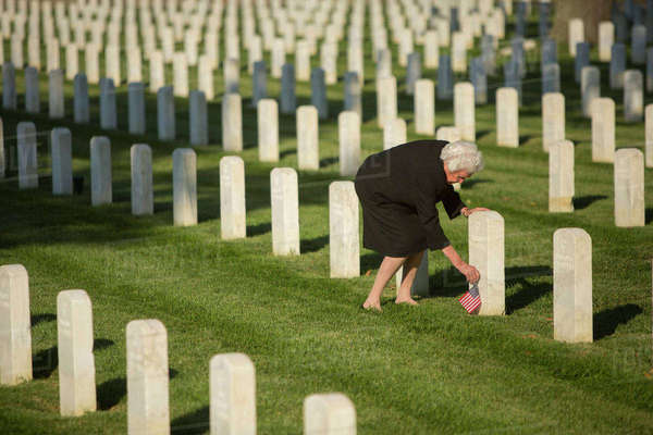 Caucasian widow placing American flag at cemetery gravestone Royalty-free stock photo