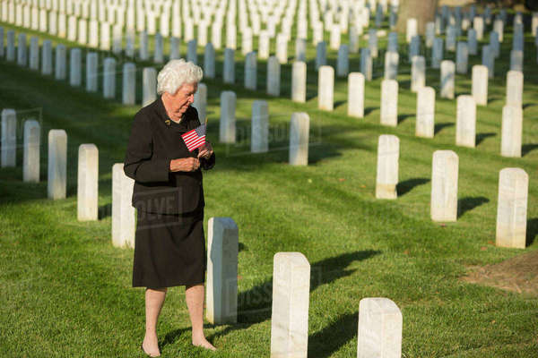 Caucasian widow holding American flag at cemetery gravestone Royalty-free stock photo
