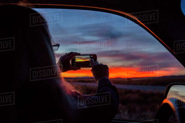 Caucasian woman in car photographing sunset with cell phone Royalty-free stock photo