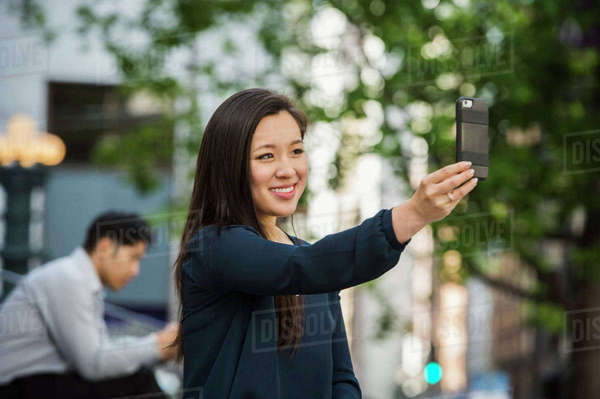 Chinese businesswoman posing for cell phone selfie outdoors Royalty-free stock photo