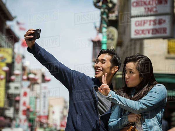 Smiling Chinese couple posing for cell phone selfie in city Royalty-free stock photo