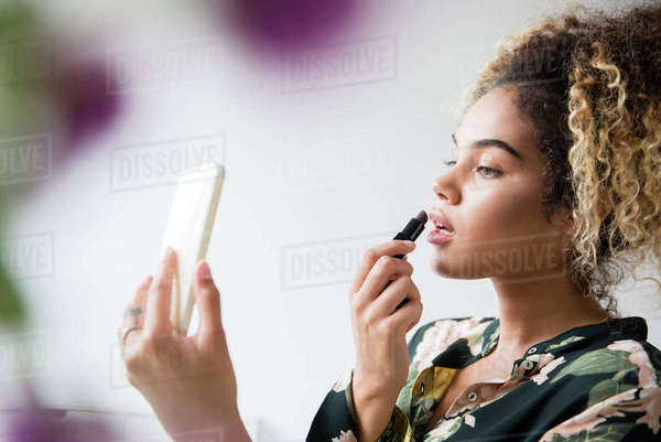 Mixed Race woman holding cell phone applying lipstick Royalty-free stock photo