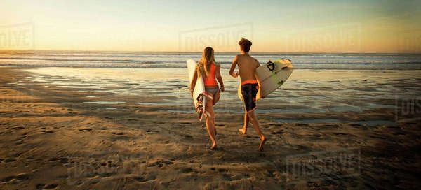 Teenage boy and girl carrying surfboards running to ocean Royalty-free stock photo